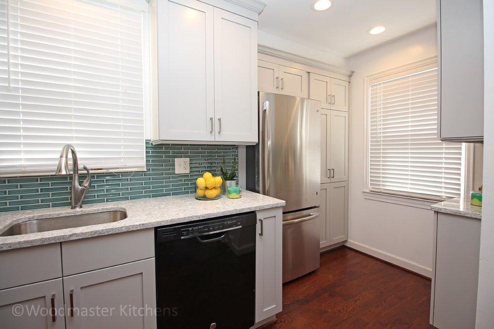 white kitchen design with teal backsplash