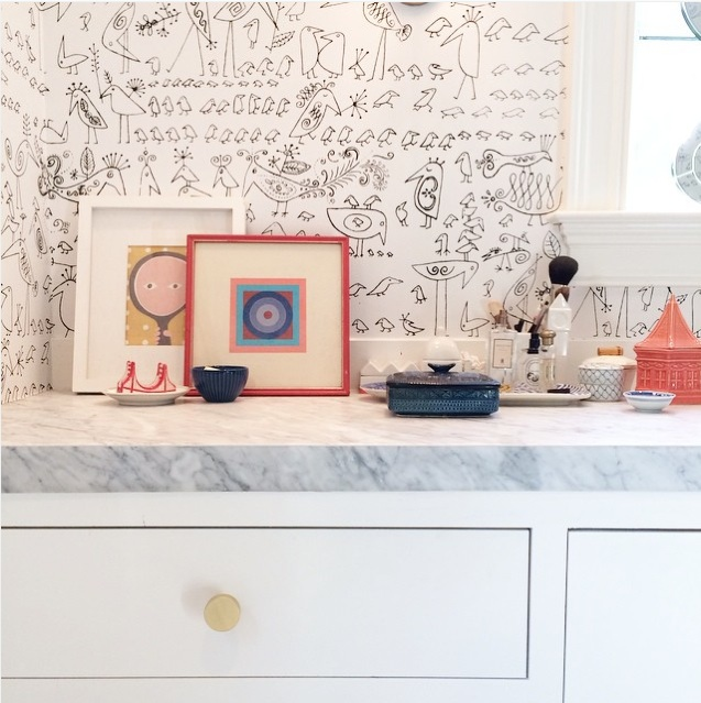 Sometimes you need a designer to sweat the details and find beauty and cohesion in new and old items. Here, pre-owned items are set against a renovated master bath complete with white cabinets, marble counter, brass knobs and a whimsical wallpaper. Photo courtesy of  Pencil and Paper Development Co.