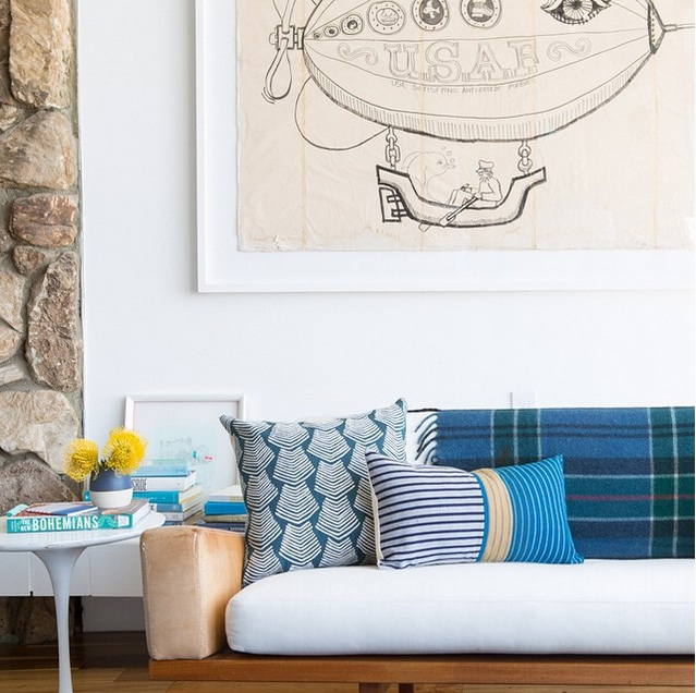 The pillows, the plaid, the white, the stone, the tulip table, the old poster art...all of this is so lovely and carefully planned out by a designer. Courtesy of  Emily Henderson.