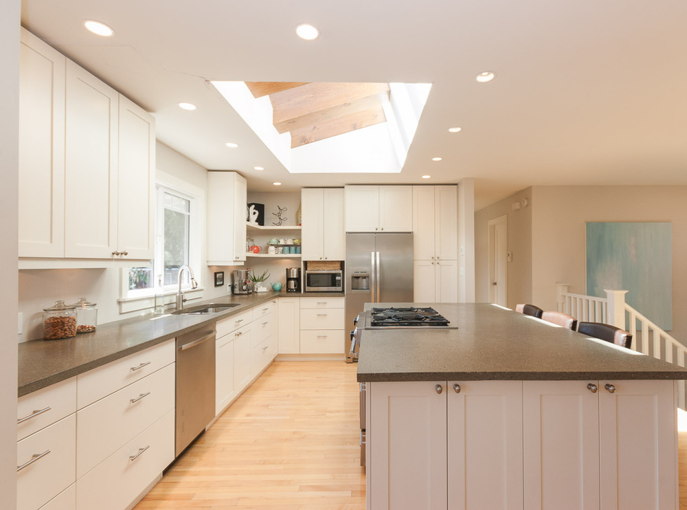 Look at how the light pours into this open kitchen from the skylights. This bi-level tore down the walls and added skylights and recessed lighting to create an airy feel. (They even added french doors to the sidewall in the dining room. Click on the photo to see the full project.)  The kitchen design and color scheme help amplify the airiness.  Photo courtesy of  Murovec Renovations Ltd.