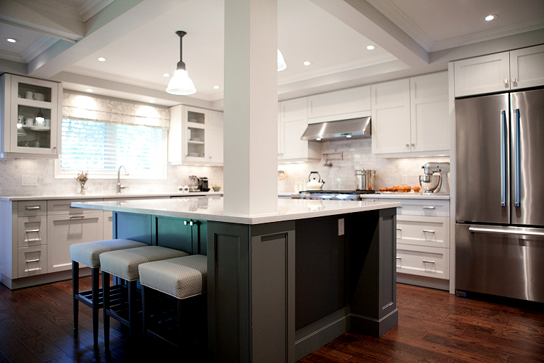 In this split, the ceilings were coffered and recessed lighting was added. A support post remains but helps frame the kitchen. This island must be amazing for entertaining and cooking. Photo courtesy of  Sweet Maple .