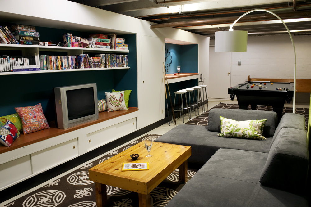 Paint your concrete basement floors and build in storage, tv & bar - and voila! You have a finished basement where the kids (and grownups) can hang out. This before can be found here.