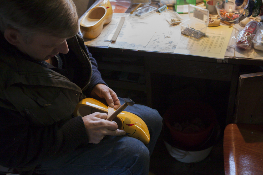 This guy is fitting a strap to the shoe - there are two styles. One that sort of covers the whole foot and this one which is a bit easier to wear and not as tight on the foot. The thing about the shoes is that they won't ever really break in - as their made of completely of wood.