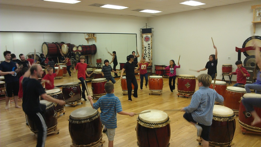 Kaminari Taiko members teach a children's taiko class. Playing taiko engages the whole body to make music.