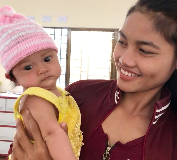 SreyMom poses proudly with her baby girl who she's able to protect and provide for through her work with Landmine Design.