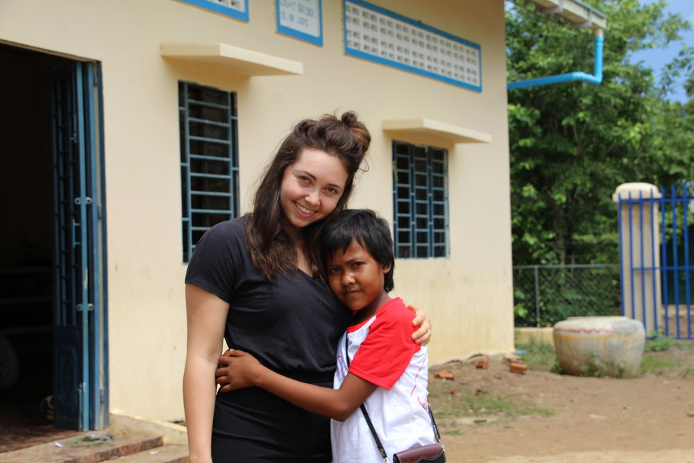 Creative Manager Kaitlyn poses with a Landmine Design artisan protege, who works alongside the women in hopes to work and safely learn with them one day.