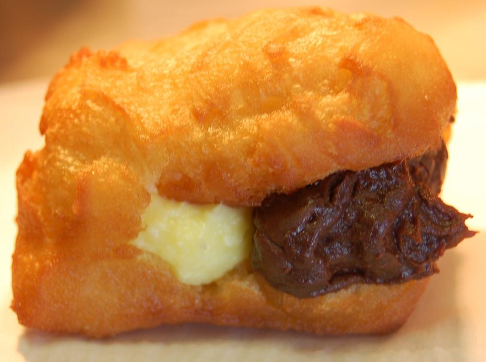 "Dough Dough's Hawaiian Malasadas malasada with lemon and chocolate filling (Photo by Lauren Lloyd)                               0    false          18 pt    18 pt    0    0       false    false    false                                               /* Style Definitions */ table.MsoNormalTable {mso-style-name:""Table Normal""; mso-tstyle-rowband-size:0; mso-tstyle-colband-size:0; mso-style-noshow:yes; mso-style-parent:""""; mso-padding-alt:0in 5.4pt 0in 5.4pt; mso-para-margin-top:0in; mso-para-margin-right:0in; mso-para-margin-bottom:10.0pt; mso-para-margin-left:0in; mso-pagination:widow-orphan; font-size:12.0pt; font-family:""Times New Roman""; mso-ascii-font-family:Cambria; mso-ascii-theme-font:minor-latin; mso-fareast-font-family:""Times New Roman""; mso-fareast-theme-font:minor-fareast; mso-hansi-font-family:Cambria; mso-hansi-theme-font:minor-latin;}                                           0    false          18 pt    18 pt    0    0       false    false    false                                               /* Style Definitions */ table.MsoNormalTable {mso-style-name:""Table Normal""; mso-tstyle-rowband-size:0; mso-tstyle-colband-size:0; mso-style-noshow:yes; mso-style-parent:""""; mso-padding-alt:0in 5.4pt 0in 5.4pt; mso-para-margin-top:0in; mso-para-margin-right:0in; mso-para-margin-bottom:10.0pt; mso-para-margin-left:0in; mso-pagination:widow-orphan; font-size:12.0pt; font-family:""Times New Roman""; mso-ascii-font-family:Cambria; mso-ascii-theme-font:minor-latin; mso-fareast-font-family:""Times New Roman""; mso-fareast-theme-font:minor-fareast; mso-hansi-font-family:Cambria; mso-hansi-theme-font:minor-latin;}"