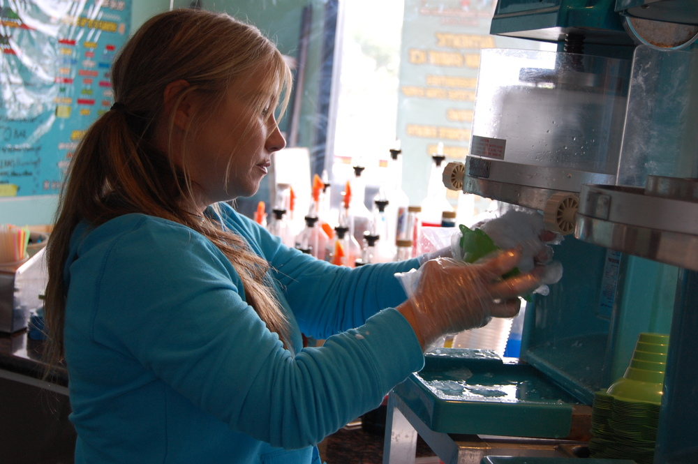 """Kelly Cartter, owner of Hula Girls Hawaiian Shave Ice, shavin' some ice (Photo by Lauren Lloyd)                               0    false          18 pt    18 pt    0    0       false    false    false                                               /* Style Definitions */ table.MsoNormalTable {mso-style-name:""""Table Normal""""; mso-tstyle-rowband-size:0; mso-tstyle-colband-size:0; mso-style-noshow:yes; mso-style-parent:""""""""; mso-padding-alt:0in 5.4pt 0in 5.4pt; mso-para-margin-top:0in; mso-para-margin-right:0in; mso-para-margin-bottom:10.0pt; mso-para-margin-left:0in; mso-pagination:widow-orphan; font-size:12.0pt; font-family:""""Times New Roman""""; mso-ascii-font-family:Cambria; mso-ascii-theme-font:minor-latin; mso-fareast-font-family:""""Times New Roman""""; mso-fareast-theme-font:minor-fareast; mso-hansi-font-family:Cambria; mso-hansi-theme-font:minor-latin;}                                           0    false          18 pt    18 pt    0    0       false    false    false                                               /* Style Definitions */ table.MsoNormalTable {mso-style-name:""""Table Normal""""; mso-tstyle-rowband-size:0; mso-tstyle-colband-size:0; mso-style-noshow:yes; mso-style-parent:""""""""; mso-padding-alt:0in 5.4pt 0in 5.4pt; mso-para-margin-top:0in; mso-para-margin-right:0in; mso-para-margin-bottom:10.0pt; mso-para-margin-left:0in; mso-pagination:widow-orphan; font-size:12.0pt; font-family:""""Times New Roman""""; mso-ascii-font-family:Cambria; mso-ascii-theme-font:minor-latin; mso-fareast-font-family:""""Times New Roman""""; mso-fareast-theme-font:minor-fareast; mso-hansi-font-family:Cambria; mso-hansi-theme-font:minor-latin;}"""