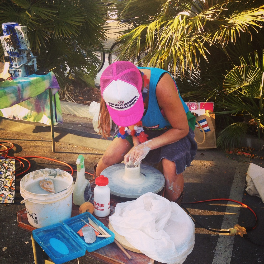 Covered in clay,  Jacqueline Marie  warms up her pottery wheel in the parking lot of the International Surfing Museum  (Photo by Lauren Lloyd)