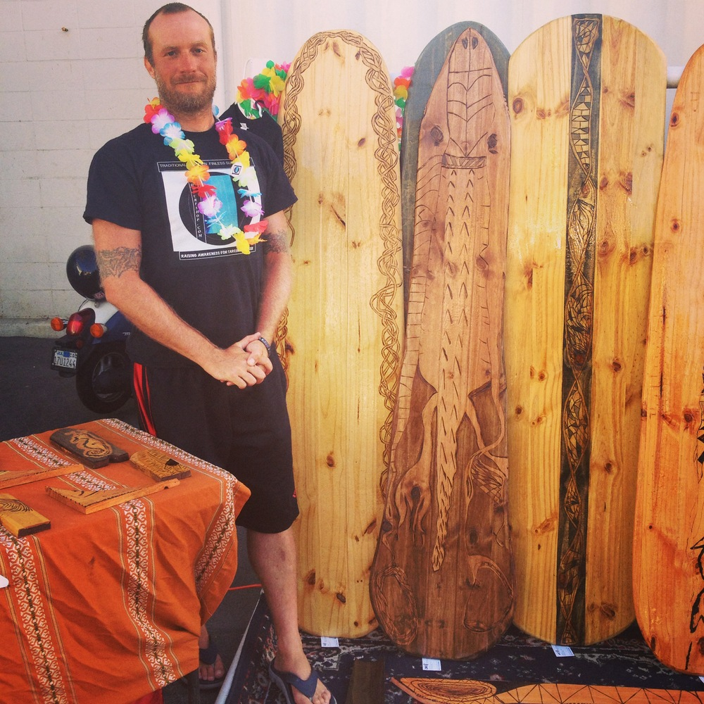 Jake from  Wow Surf Shop  in Sunset Beach stands with his stunning collection of handmade wood Alaias  (Photo by Lauren Lloyd)