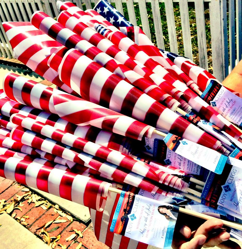 """Realtor Jody Clegg distributes American flags to homes in downtown HB!""  (Photo by Larry Tenney)"