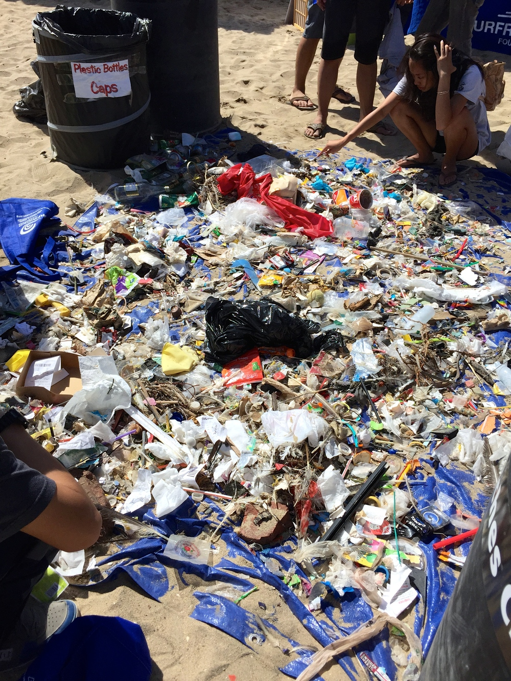 Sorting the findings from the  Reduce, Reuse, Recycle Surf Off Surfrider beach cleanup.   (Photo by Lauren Lloyd)