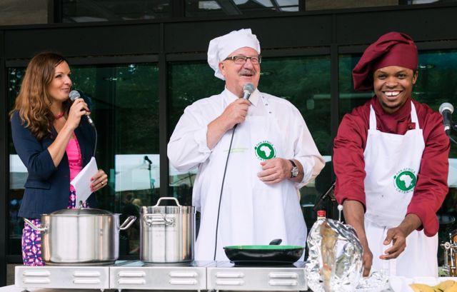 Moderatorin Iza Höll, Staatssekretär Hans Joachim Fuchtel und Panafrika Koch Frank Anjangbe bei der Kochshow am Tag der offenen Tür 2014 im BMZ