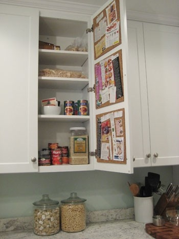 Cork tiles inside a kitchen cabinet.  Clear the counter clutter (say that three times fast) and make recipes and shopping lists easily accessible.  Genius.