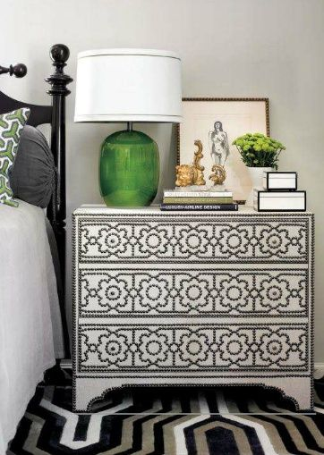 The black, traditional bed pairs wonderfully with the nail trim, upholstered nightstand.