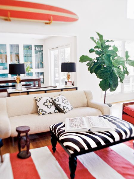 The sofa serves as a neutral backdrop for the red and blue accents in the room.