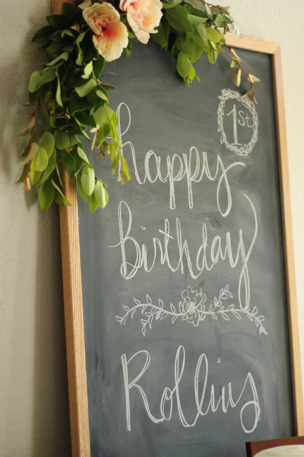 chalkboard first birthday with flower garland