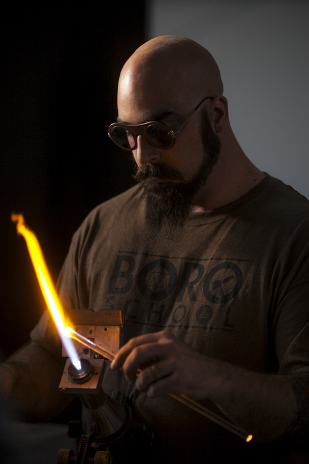 "Nathan Aweida teaches a class at The Boro School, his new glassmaking school concentrating on borosilicate glass, Tuesday April 1, 2014. Aweida owns 7 Point Studios on Dearborn Street, a collection of studios rented to artists and entrepreneurs, and opened The Boro School in January 2014. He has been working with glass for 12 years, and just started offering pipe making classes for beginners. ""It's kind of mesmerizing,"" said Aweida about the difference of soft glass blowing and borosilicate glass. ""There's something about being able to work this closely with the material. You're just right there, hugging the flame."""