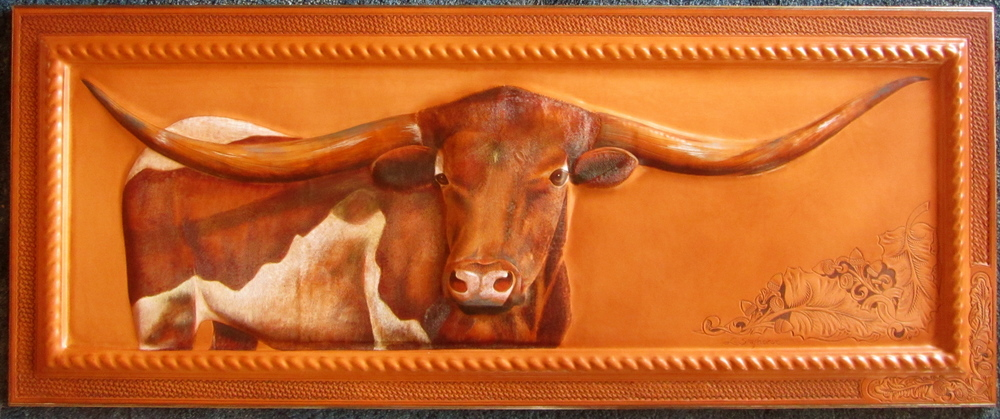 """The Boss""                 14"" X 42""               $3800                   Mixed media on leather    We used a very unique process on this piece. The subject and the frame are all one piece of leather! The longhorn is sculpted, and painted. The leather continues over the frame for more sculpting  and then additional tooling is done on the flat edge of the frame. Truly a one-of-a-kind!"