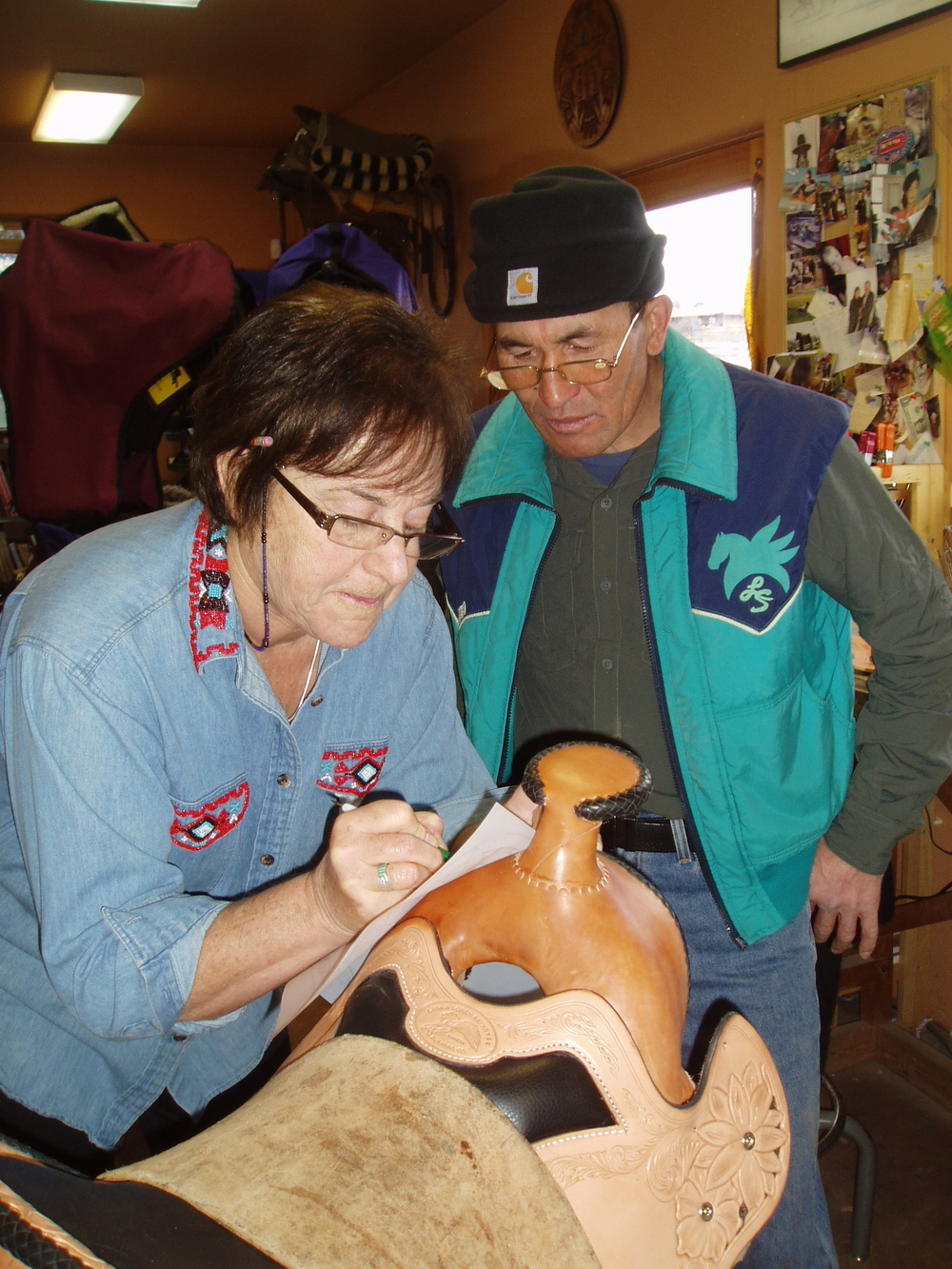 Lisa  showing Seremei how to transfer a design to the front of a saddle.