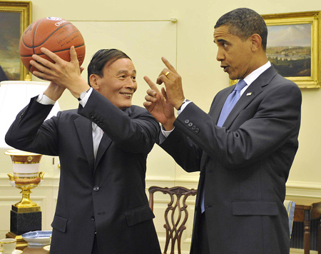 Vice Premier Wang Qishan accepting a basketball as a gift from President Barack Obama