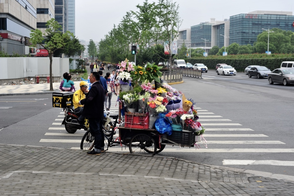 The flower vendor on this busy street corner always sells the most beautiful flowers, and for a good price too.  这个卖花的人卖又漂亮又香的花,价格也很便宜。