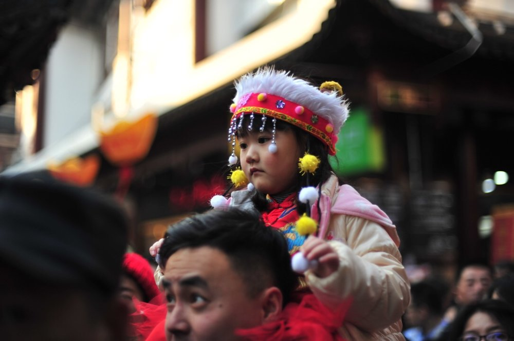 A little girl dons a traditional hat.