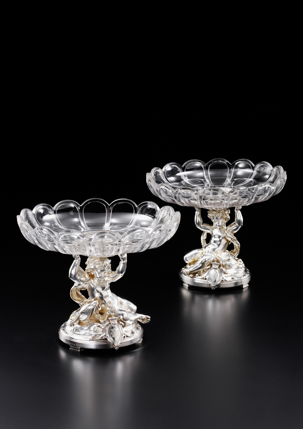 CHRISTOFLE & CIE     A pair of circular table centrepieces      Paris, circa 1870    Silver and glass    Representing a winged angel hanging in a shell holding a   small dish in cut glass, and a fish swimming beside. The base is ornamented with a medallion with an engraved arms of a   Spanish Marquis    15.8 x 16.2 cm    Weight 2468 gr.