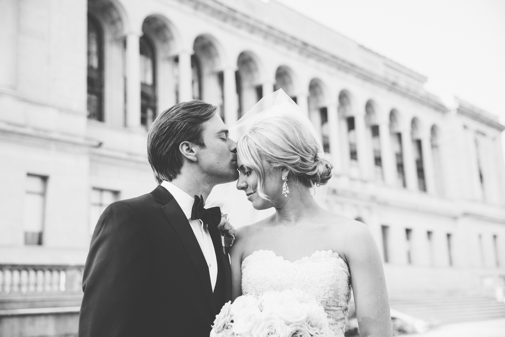 groom kissing bride in front of city hall architecture on wedding day