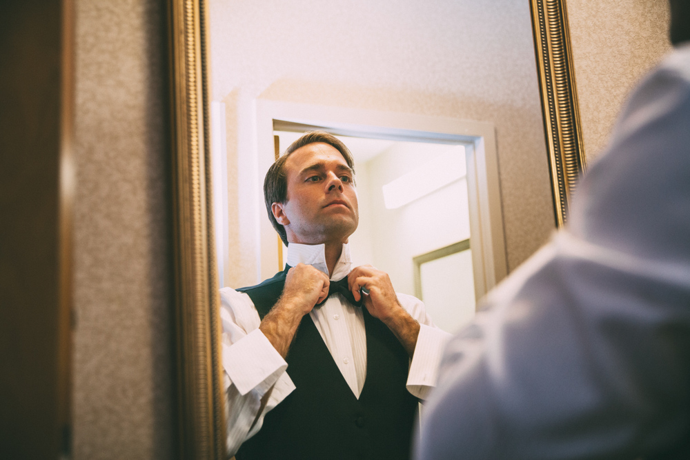 Groom ties tie in mirror