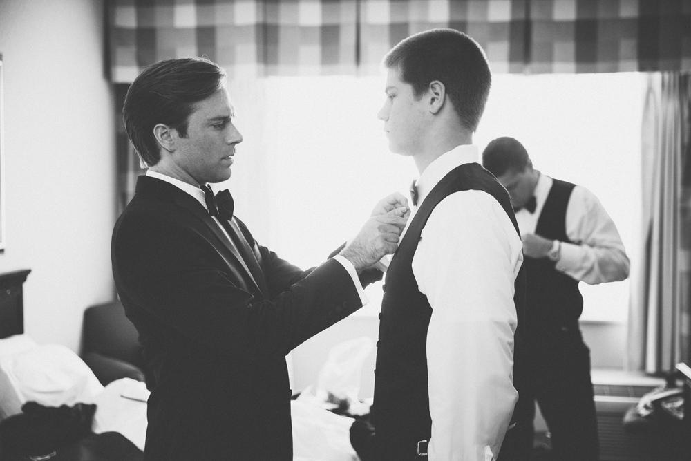 Groom helps groomsman with tie