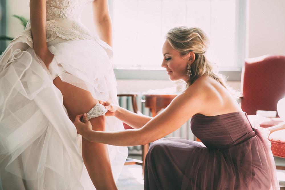 Bride puts garter belt on under wedding dress