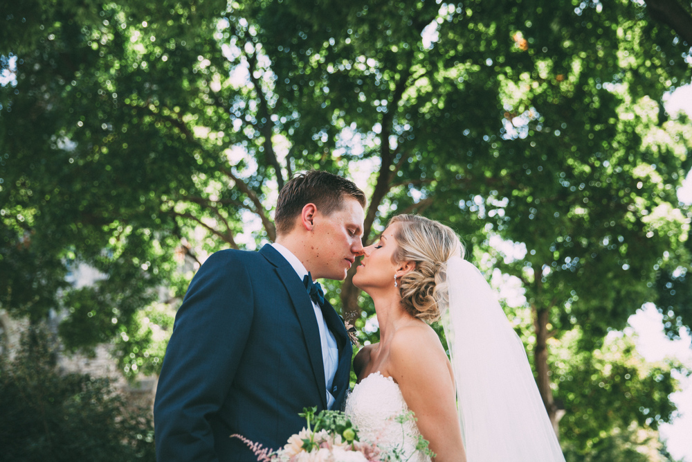 Bride and Groom kissing under trees