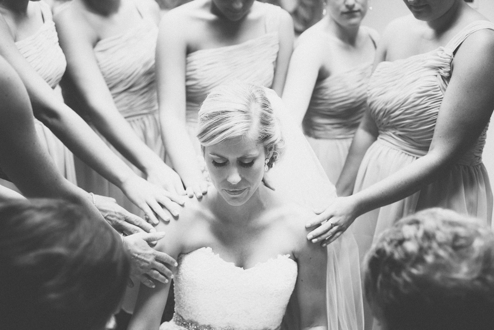 Bridesmaids pray over the bride before the wedding ceremony