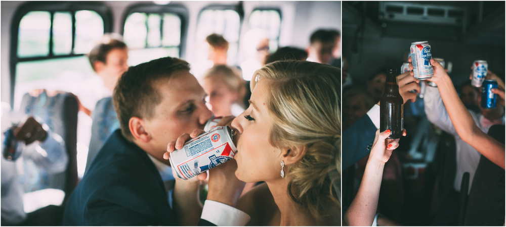 Bride and groom share drinks on the bus after their wedding