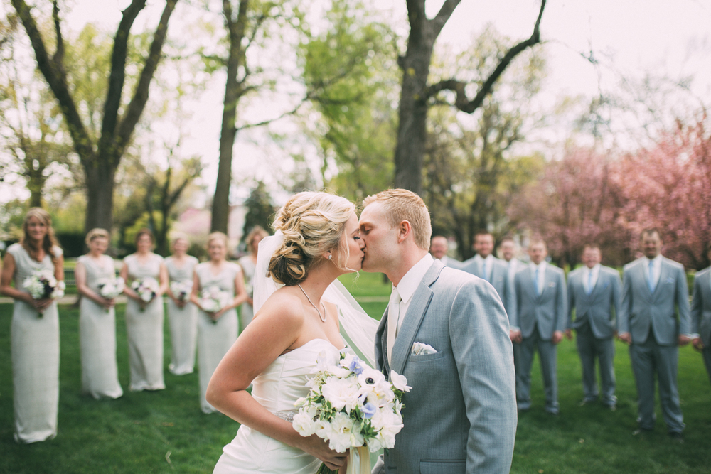 Bride and groom kissing in front of wedding bridal party in spring