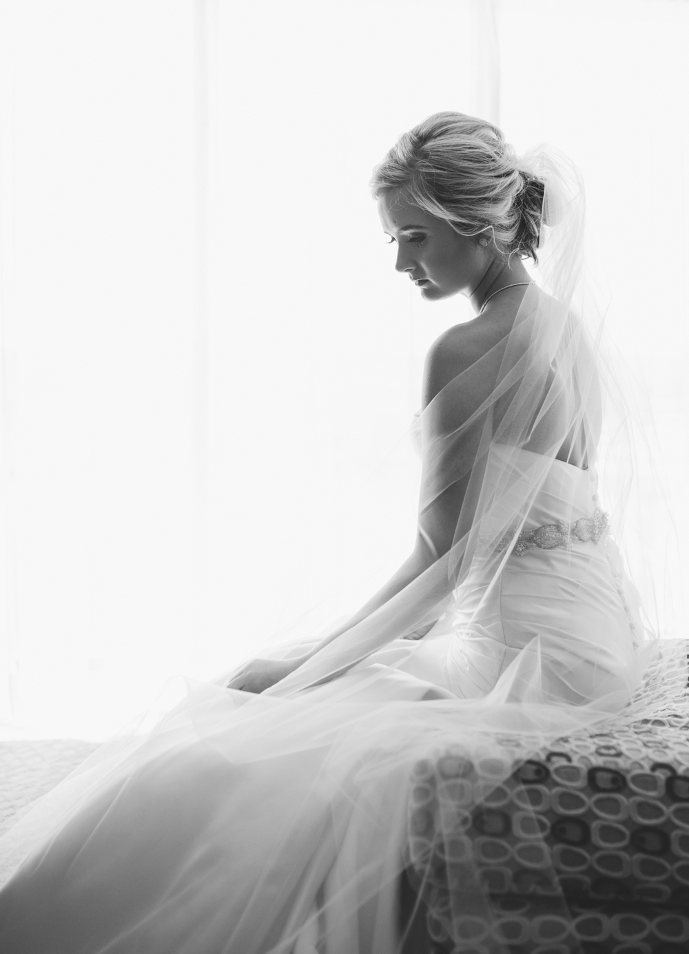 Beautiful bride in front of window looking down in black and white