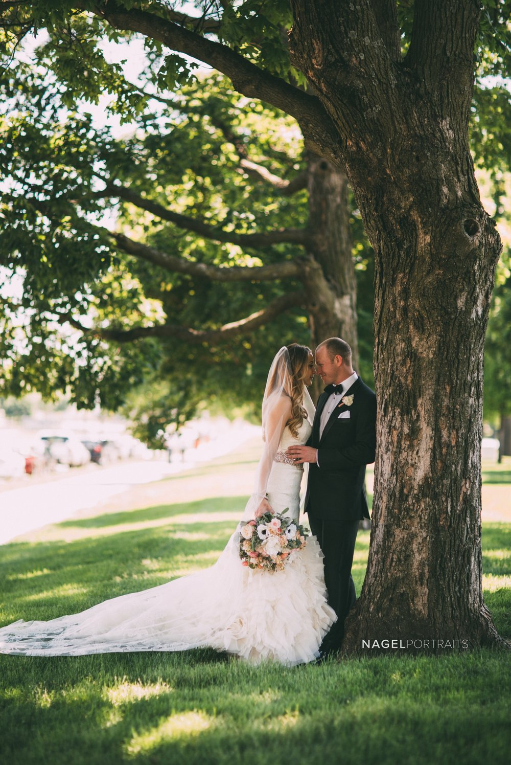 portrait of bride and groom under tree on wedding day