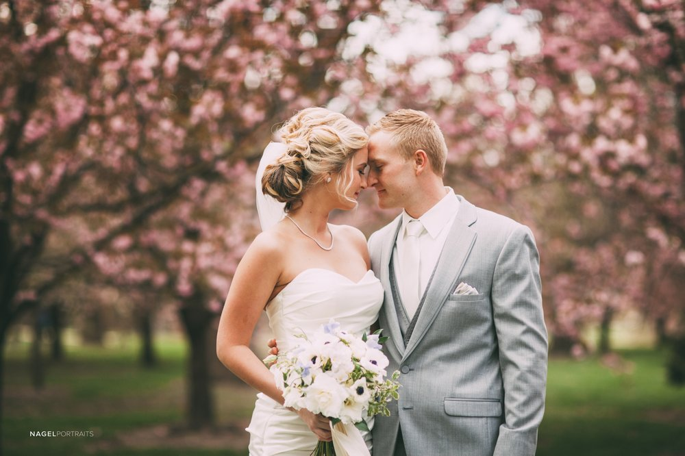 bride and groom in front of beautiful spring trees in the park