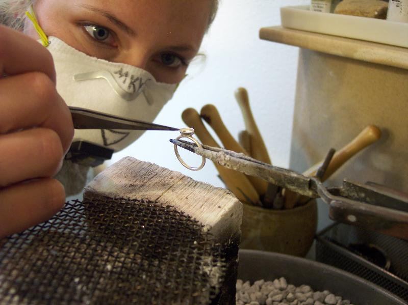 Metal and goldsmith, Miranda Kyger, works on a custom bezel setting