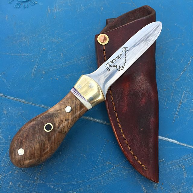 For Sale! Oyster knife with wampum inlay from @rachelmeowww  Stabilized oak burl from Martha's Vineyard and ebony wood in the center pin.  Blade is etched with Martha's Vineyard outline. Leather belt sheath. $550, DM me if you're interested!  #oysterknife #theofficialoysterknifeofcapecod #marthasvineyard #wampum #capemade