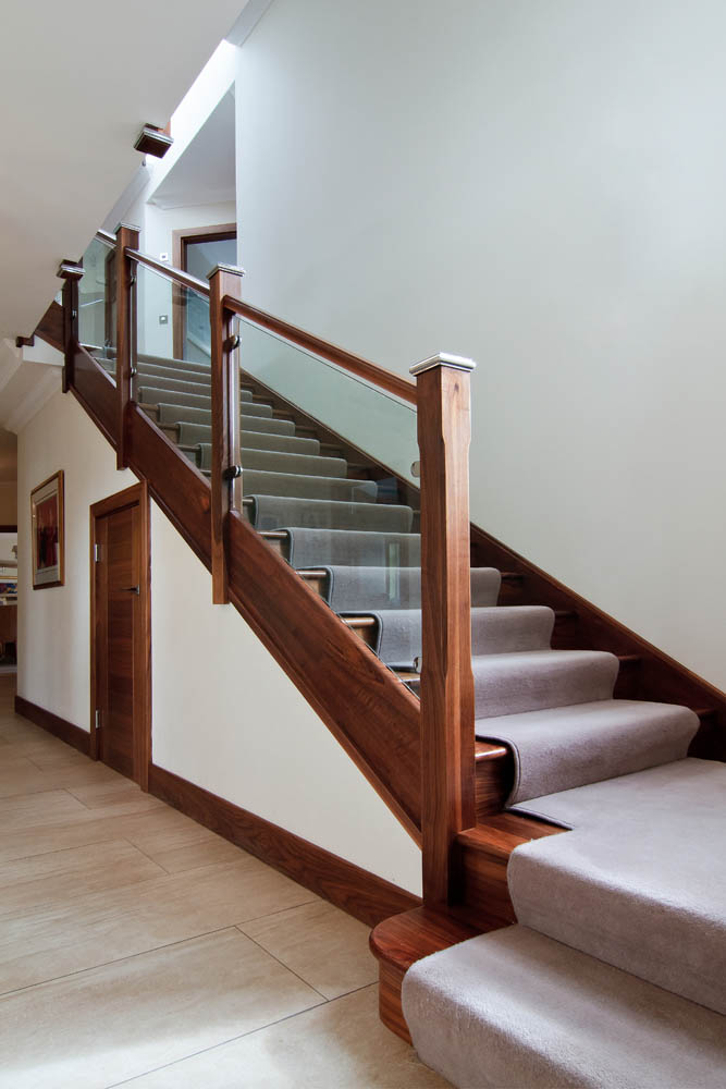 www.stockwell-ltd.co.uk   Walnut and glass dogleg stair with feature curved top step.