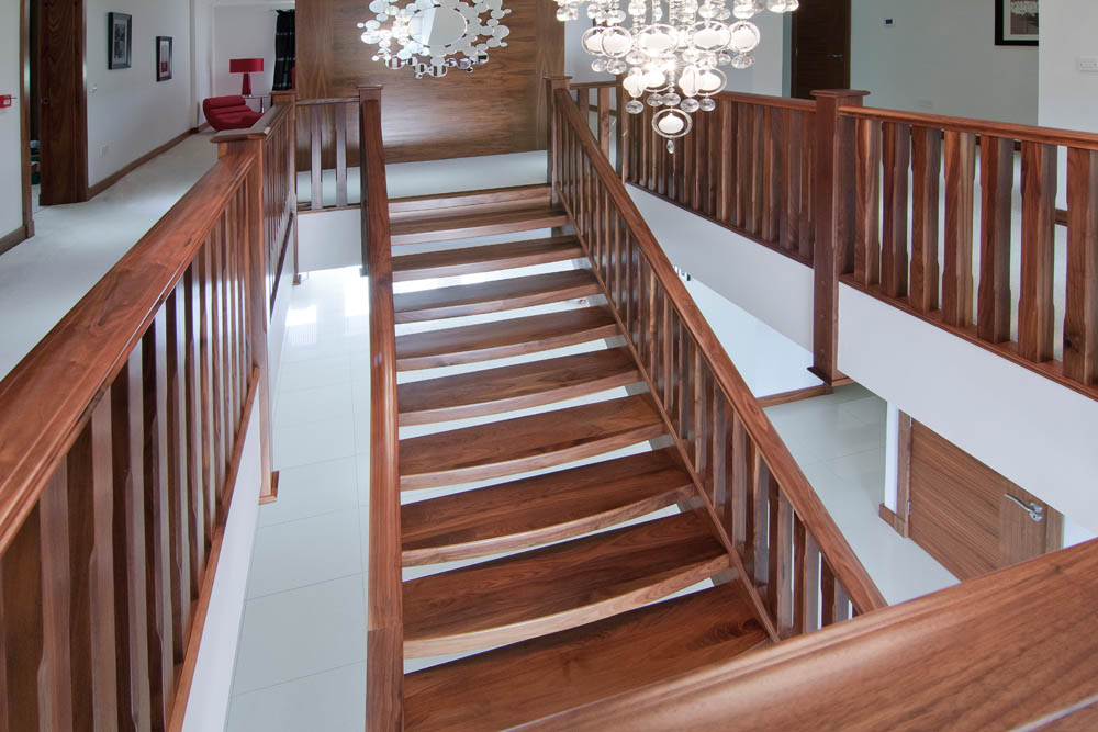 www.stockwell-ltd.co.uk   Curved and splayed walnut open-riser staircase with curved sleeper treads and chamfered balustrading.
