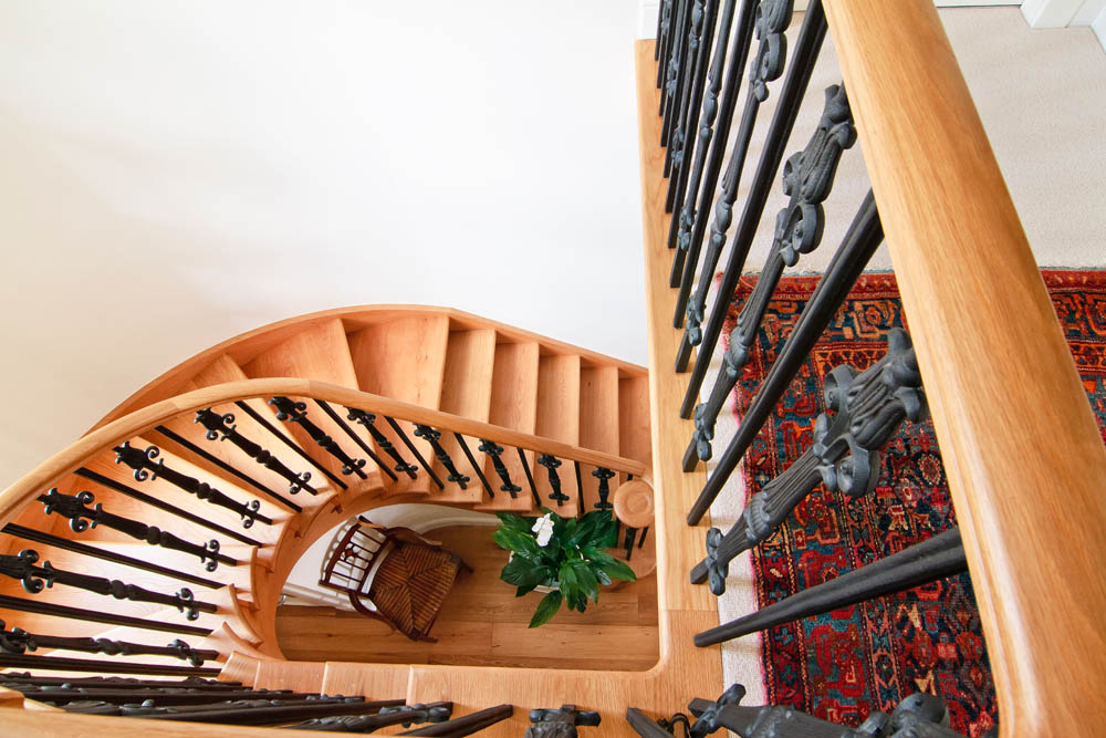 www.stockwell-ltd.co.uk   Curved, cut-stringer, american white oak staircase with continuous handrail and bespoke wrought-iron spindles.