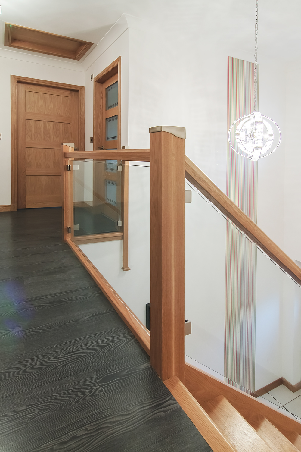 www.stockwell-ltd.co.uk   White oak o  pen-rise bottom winder stair   with brushed nickel riser rods and glass balustrade.