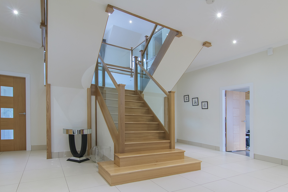 www.stockwell-ltd.co.uk    American white oak 3 part dogleg flight   stair   with square feature curtail platform, square curtail step, square newels, glass balustrade and finished with a sprayed clear satin lacquer.