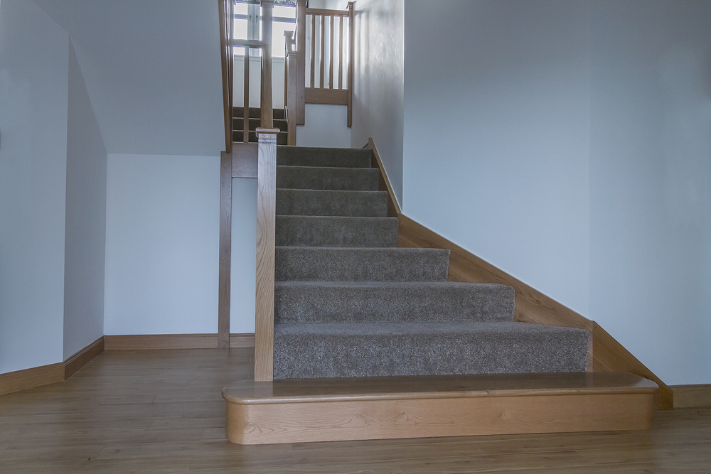 www.stockwell-ltd.co.uk   3 part dogleg oak staircase with feature splayed wall stringer, curtail step, square newels with walnut inlay and square spindles.