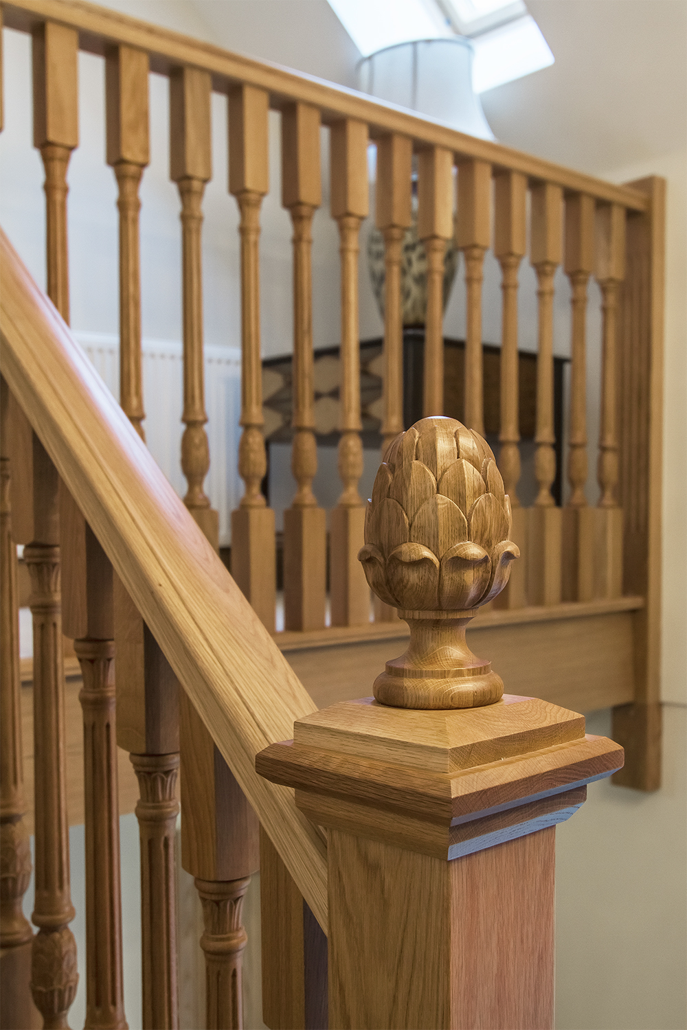 www.stockwell-ltd.co.uk   3 part cut stringer dogleg   oak stair   with feature curved   curtail tread  , fluted   newels, turned & fluted spindles and customer-  designed newel caps featuring   hand-carved   artichoke   caps  .