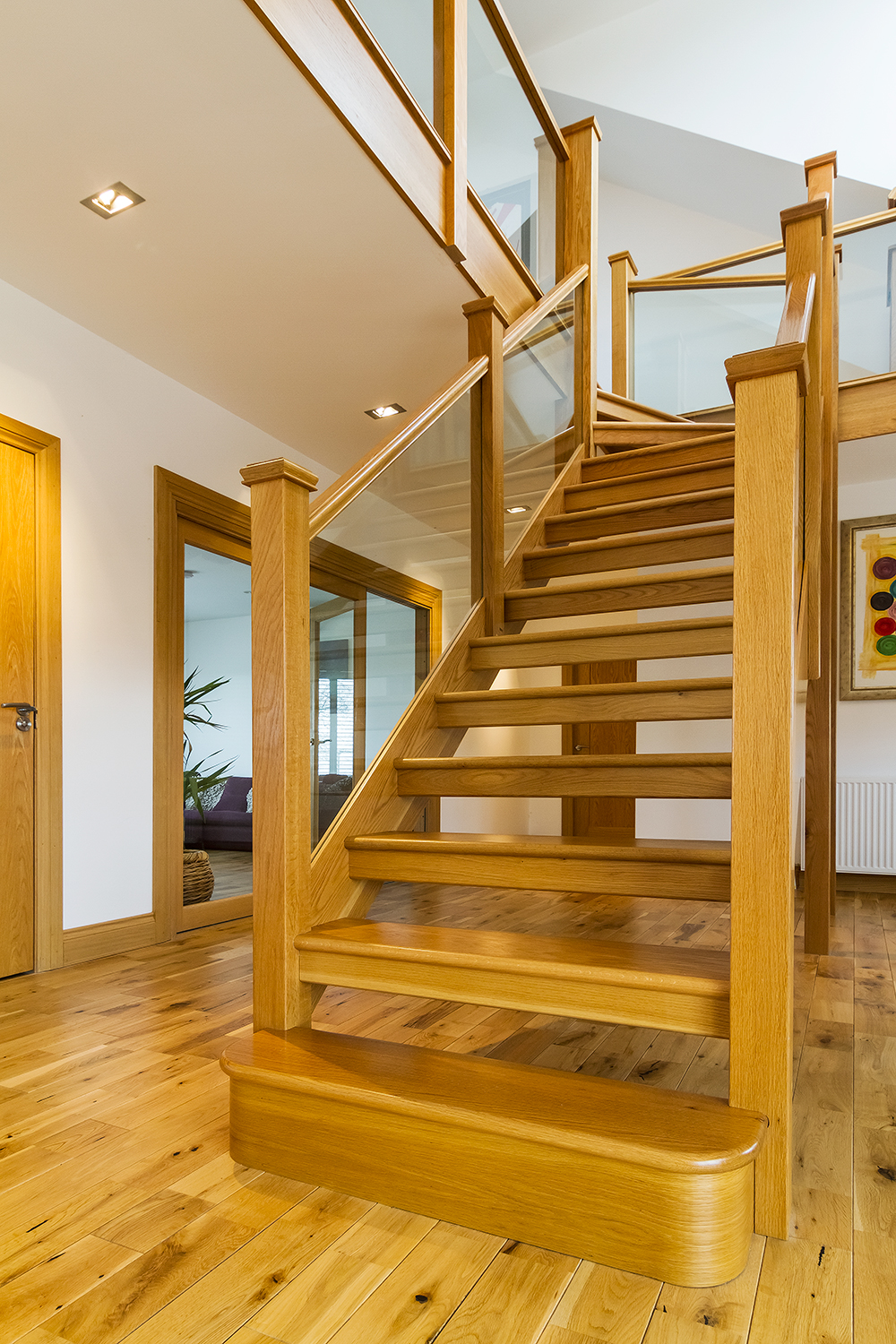 www.stockwell-ltd.co.uk   3 kite top winder open rise   stair in American white oak with a double bull  nose tread,   glass panel picture-  frame bal  ustrade   and pyramid   newel caps  .