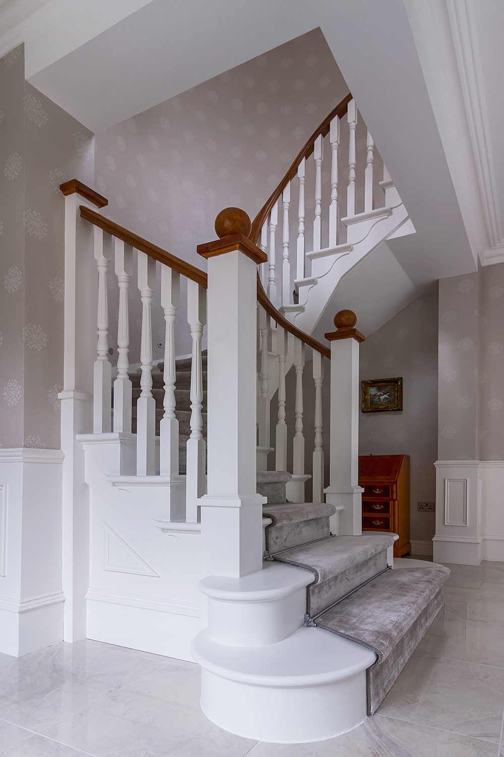 www.stockwell-ltd.co.uk   Bespoke c  urved cut-stringer staircase with white oak lacquered curved handrail and newel caps  . This stair is highly detailed with stringer capes, curved scotia beading and double curtail steps.
